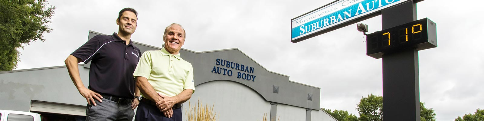 The owners of Suburban Auto Body standing in front of one of their locations in the Twin Cities